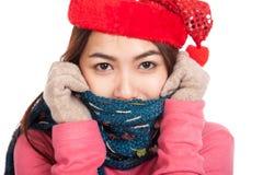 Den lyckliga asiatiska flickan med röd jul hatt och halsduk känner förkylning Arkivfoton