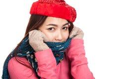 Den lyckliga asiatiska flickan med röd jul hatt och halsduk känner förkylning Arkivbilder