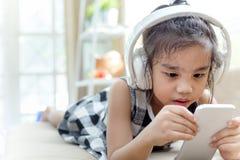 Den lyckliga asiatiska flickan som använder headphonen för, lyssnar musik vid smartphonen Arkivfoton