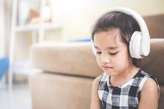 Den lyckliga asiatiska flickan som använder headphonen för, lyssnar musik vid smartphonen Royaltyfri Bild