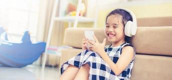 Den lyckliga asiatiska flickan som använder headphonen för, lyssnar musik vid smartphonen medan i det levande rummet Royaltyfria Foton
