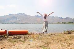 Den lyckliga asiatiska kvinnan i kläder för tillfällig stil lyftte upp armar och att stå i floden med bergsikt arkivbilder