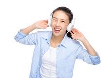 Den lyckliga asiatiska kvinnan lyssnar till sången vid headphonen Royaltyfri Bild