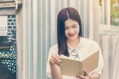 Den lyckliga asiatiska kvinnan tycker om att läsa som är utomhus- fotografering för bildbyråer