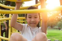 Den lyckliga asiatiska lilla flickan som spelar på en utomhus- lekplats och ser kameran i, parkerar, sommar, semesterbegrepp arkivfoto