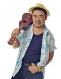 Den lyckliga asiatiska mannen bär ukuleleisolatbakgrund Fotografering för Bildbyråer