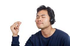 Den lyckliga asiatiska mannen lyssnar till musik fingrar att låsa fast Arkivfoton