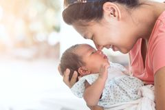 Den lyckliga asiatiska modern som kramar och kysser hennes nyfött, behandla som ett barn Arkivfoton
