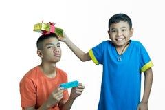 Den lyckliga asiatiska ungen ger gåva till hans broder Arkivfoton