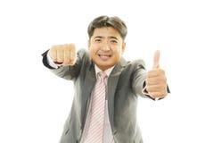 Den lyckliga asiatiska visningen för affärsman tummar upp tecken royaltyfri foto