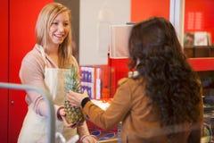 den lyckliga assistentkunden shoppar supermarketen royaltyfria foton