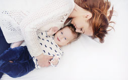 Den lyckliga att bry sig modern med hennes gulligt behandla som ett barn pojken Fotografering för Bildbyråer
