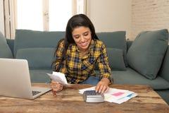 Den lyckliga attraktiva kvinnan som hem beräknar finanser och att betala fakturerar hemma genom att använda räknemaskinen och bär royaltyfria foton