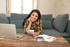 Den lyckliga attraktiva kvinnan som hem beräknar finanser och att betala fakturerar hemma genom att använda räknemaskinen och bär arkivfoton