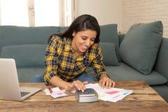 Den lyckliga attraktiva kvinnan som hem beräknar finanser och att betala fakturerar hemma genom att använda räknemaskinen och bär royaltyfri foto