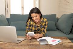 Den lyckliga attraktiva kvinnan som hem beräknar finanser och att betala fakturerar hemma genom att använda räknemaskinen och bär Royaltyfri Fotografi