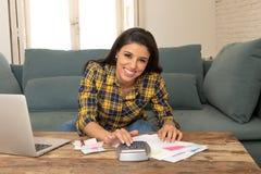 Den lyckliga attraktiva kvinnan som hem beräknar finanser och att betala fakturerar hemma genom att använda räknemaskinen och bär Royaltyfri Bild
