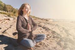 Den lyckliga avkopplade unga kvinnan som mediterar i en yoga, poserar på stranden royaltyfria bilder