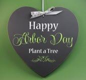 Den lyckliga axeldagen planterar ett träd som hälsar meddelandetecknet på den hjärta formade svart tavla Royaltyfri Foto