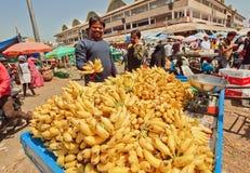 Den lyckliga bananaffärsmannen som säljer frukter på fullsatta bönder, marknadsför Fotografering för Bildbyråer
