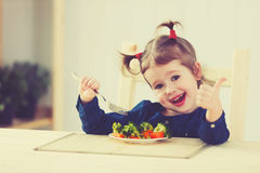 Den lyckliga barnflickan äter upp grönsaker och visningtummar royaltyfri fotografi