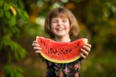 Den lyckliga barnflickan äter vattenmelon i sommar arkivbilder