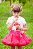 Den lyckliga barnflickan dricker fruktsaft Royaltyfri Bild