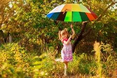 Den lyckliga barnflickan g?r med det m?ngf?rgade paraplyet under regn arkivbilder
