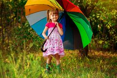 Den lyckliga barnflickan g?r med det m?ngf?rgade paraplyet under regn fotografering för bildbyråer