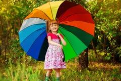 Den lyckliga barnflickan g?r med det m?ngf?rgade paraplyet under regn arkivbild