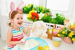 Den lyckliga barnflickan målar ägg för påsk Arkivbilder