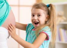 Den lyckliga barnflickan omfamnar hennes gravida moder Arkivbild