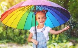 Den lyckliga barnflickan skrattar och spelar under sommarregn med en umbr Royaltyfria Bilder