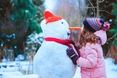 den lyckliga barnflickan som har gyckel och bygger snögubben på vinter, går i snöig trädgård arkivfoton