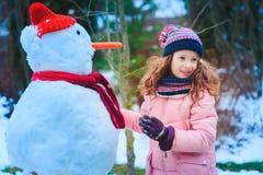 den lyckliga barnflickan som har gyckel och bygger snögubben på vinter, går i snöig trädgård royaltyfri foto