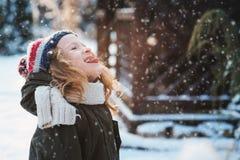 Den lyckliga barnflickan som spelar med snö på snöig vinter, går på trädgård Royaltyfria Foton