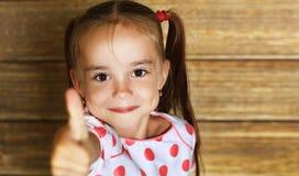 Den lyckliga barnflickavisningen tummar upp royaltyfria foton