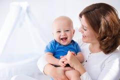 Den lyckliga barnmodern med behandla som ett barn pojken hemma royaltyfria foton