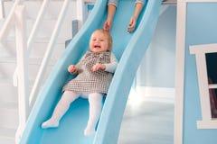 Den lyckliga barnmodern med hennes behandla som ett barn pojken som spelar i den färgrika lekplatsen för ungar Arkivfoton