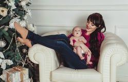 Den lyckliga barnmodern med kalt nyfött behandla som ett barn sammanträde i fåtölj i dekorerat rum för jul arkivfoto