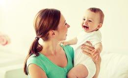 Den lyckliga barnmodern med lite behandla som ett barn hemma royaltyfri bild