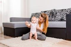 Den lyckliga barnmodern som spelar med henne, behandla som ett barn på golvet nära soffan arkivfoto