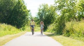 Den lyckliga barnparridningen cyklar i sommar arkivfoton