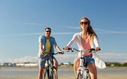 Den lyckliga barnparridningen cyklar på sjösidan arkivfoto