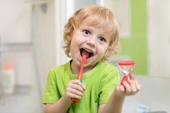 Den lyckliga barnpojken som borstar tänder nära, avspeglar i badrum Han övervakar att vara av lokalvårdhandling med timglas Arkivfoto