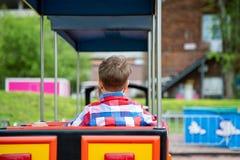 Den lyckliga barnpojken som har gyckel parkerar in Ta en ritt behandla som ett barn på drevet Arkivbild