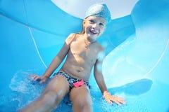Den lyckliga barnrullningen från glidbana i vatten parkerar Royaltyfri Foto