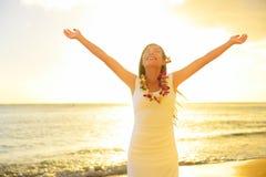 Den lyckliga bekymmerslösa kvinnan frigör i Hawaii strandsolnedgång Royaltyfri Bild