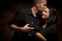 Den lyckliga blandade racen kopplar ihop att flörta och hållande Wineexponeringsglas royaltyfria bilder