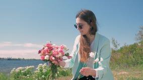 Den lyckliga blomsterhandlarekvinnlign i exponeringsglas samlar buketten av härliga blommor utomhus arkivfilmer